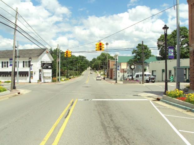 This is an image of a typical suburban crossroads. It is a bright, sunny day, and a traffic light hangs over the intersection.