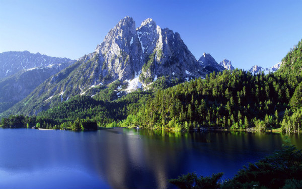 This is an image of a mountain range and its reflection in a nearby body of water.
