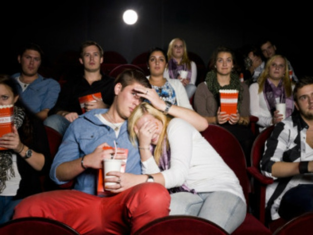 This image shows a crowd of people in a movie theater watching a movie.